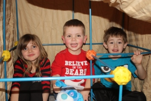Jayden and his birth siblings sitting in their fort that they build with his birth father.